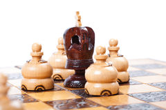 Chess game with black king surrounded by opposing pawn Stock Photo