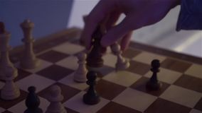 Chess Game Chess Board. Caucasian white male hands at evening dark night scene with camera movement shot in slow motion with dynamic color of light stock video footage