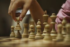 On a chess game, a chess player makes a move with a pawn royalty free stock image