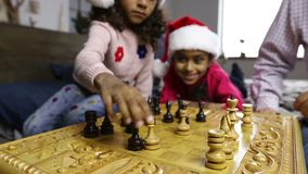 Chess game for clever minds on winter holidays. Diverse family playing chess during christmas at home. Selective focus on players hands moving chess pieces stock video footage