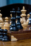 Chess game, close up of a black king and queen, other figures in the front Royalty Free Stock Photo