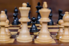 Chess game, close up of a black pawn, white figures in the front Royalty Free Stock Photography