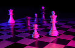 Chess game dark. Chess pieces gelled on dark background Royalty Free Stock Images