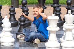 Chess game with giant chess piece. Boy playing strategic outdoor game on black and white board. Chess game with giant chess piece. Boy playing strategic outdoor stock image