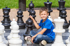 Chess game with giant chess piece. Boy siting and playing strategic outdoor game on black and white board. Chess game with giant chess piece. Boy siting and stock photo