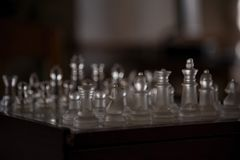 Chess game with glass pieces in light Stock Photography