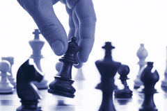 Chess game make your move. Blue tone close up of hand and chess pieces Royalty Free Stock Images