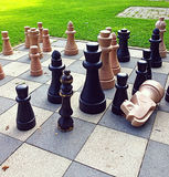 Chess game outdoors. Chessboard with big size wooden figures outdoors in the park Stock Image