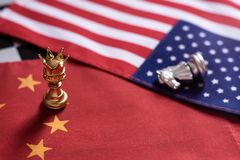 Chess game. Pawns with golden crown stand as winner over the knight on China and USA national flags. Trade war concept. Copy space, against, battle, business stock photos