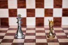 Chess game. Small pawn wearing golden crown stand confront the king. Business competitive and challenging. Copy space, achievement, adrenaline, ahead, ambition stock photo