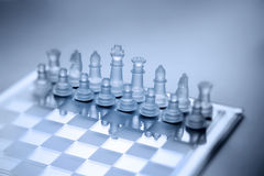Chess Game Strategy Background. Chess pieces set up ready for play on a chess board with focus centered on the king and queen Royalty Free Stock Photos