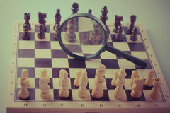 Chess game strategy with chess pieces and magnifying glass, vintage style Royalty Free Stock Photography