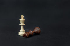 Chess game. White and black king challenging for victory. Isolated on black background Royalty Free Stock Photography