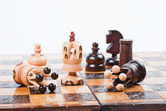 Chess game with white chess king between fallen queens. White Chess King between fallen queens win the game, surrounded by pawn, knight and rook, on old wooden royalty free stock photo