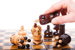Chess Game with white King on wooden Chessboard checkmated by opposing King. White chess king checkmated by the black king and falling down on old wooden stock photography