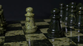 Chess game. White pawn defeats black pawn. Selective focus. Chess pawn defeated pawn. Details of chess piece on black. Background 4K Stock Photos