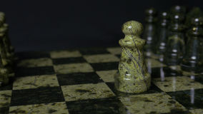 Chess game. White pawn defeats black pawn. Selective focus. Chess pawn defeated pawn. Details of chess piece on black. Background 4K Royalty Free Stock Image