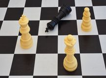 Chess game. White chess pieces on a board and one black piece lying. Chess game with plastics pieces. White chess pieces are winning, one black piece is lying stock photos