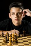 Chess game. An 11 year old thinks about his next move during a chess game stock photo