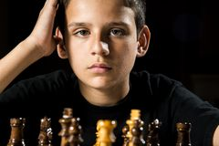 Chess game. An 11 year old thinks about his next move during a chess game royalty free stock photography