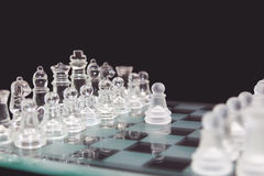 Chess of glass on a black background, the beginning of the game. Royalty Free Stock Photo