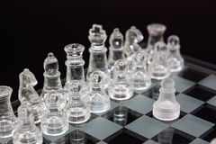 Chess of glass on a black background, the first move of the game. Royalty Free Stock Photography
