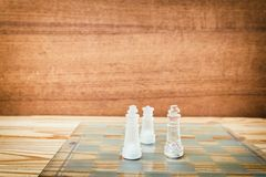 Chess glass on board in game. On a vintage wooden floor background vintage scratched old film colors. Concept competition business. Success. with copy space add stock photo