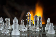 Chess Glass Figures. A shot of chess figures in front of the fire Royalty Free Stock Photos