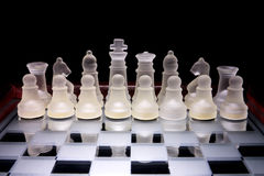 Chess. Glass chess on a glass stand chessboard Stock Image