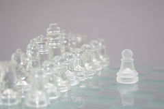 Chess of glass on a gray background, the beginning of the game. Stock Photography