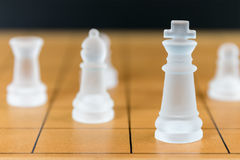 Chess glass on a wood chessboard Stock Photography