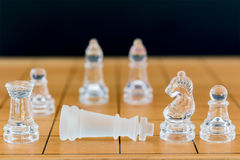 Chess glass on a wood chessboard Stock Photos