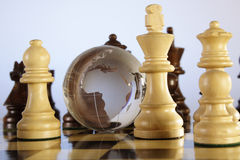 Chess and globe. A crystal globe is placed in between the chess pieces Royalty Free Stock Photography