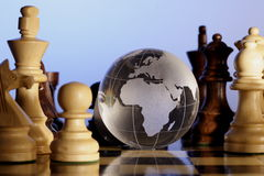 Chess and globe. A crystal globe is placed in between the chess pieces Royalty Free Stock Photos