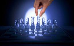 Chess Hand Business Strategy. A chessboard with a hand starting to move a  chess piece Royalty Free Stock Photo