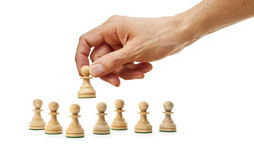 Chess Hand Strategy Business. A hand holding a pawn chess piece with other pawns on a white background Stock Photos