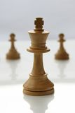 Chess King. White wooden chess king with pawns in background royalty free stock photos