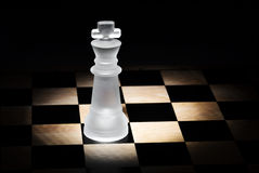Chess king. On a board, with black background Stock Photos