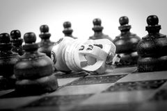 Chess King checkmated by many opposing pawn, black and white,. Checkmated King on old wooden Chessboard with black pawn around, textured background, black and royalty free stock photo