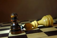 Chess king defeated by pawn. Defeat and Victory. Concept with wooden chess pieces Royalty Free Stock Images