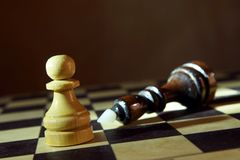Chess king defeated by pawn. Victory in unequal fight Stock Image
