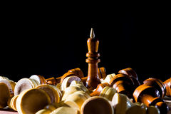 Chess king among fallen chess pieces. Black wooden chess king among fallen chess pieces with dark background Stock Photos