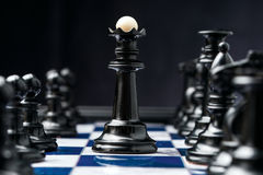 Chess king. Among his black pieces royalty free stock images