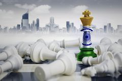 Chess king with India flag defeating rivals. Image of a chess king with India flag defeating white chess pieces. Shot with modern city Royalty Free Stock Images