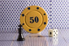 Chess king and other objects for popular board games. A dice and a poker chip on the back of the playing cards Royalty Free Stock Photography
