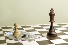 The chess king, pawn and money on a chessboard Royalty Free Stock Image