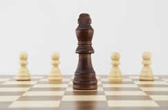 Chess king and pawns on chessboard Royalty Free Stock Image