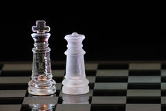 Chess King And Queen. Two chess pieces on a glass board showing a king and the queen royalty free stock image