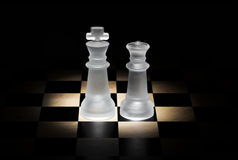Chess. King and queen on a board, with black background Stock Photos