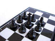 Chess king stands on a chess board with figures stock photography
